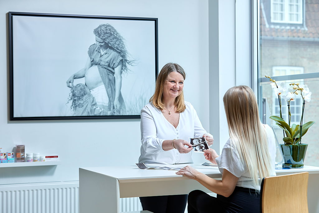 Kunde får overrakt graviditets scanningsbilleder