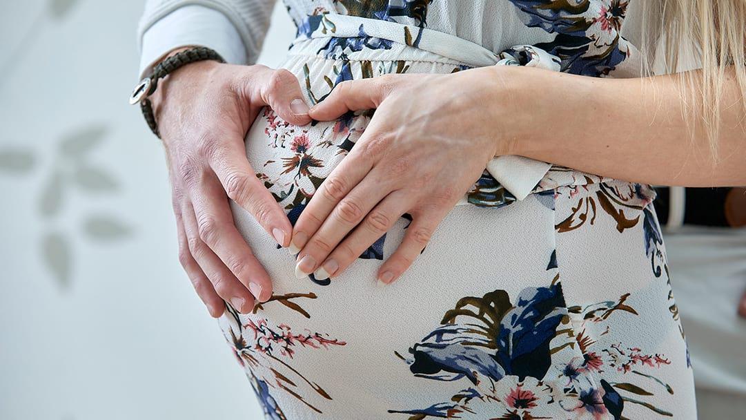 holder om maven til graviditetsscanning i Odense