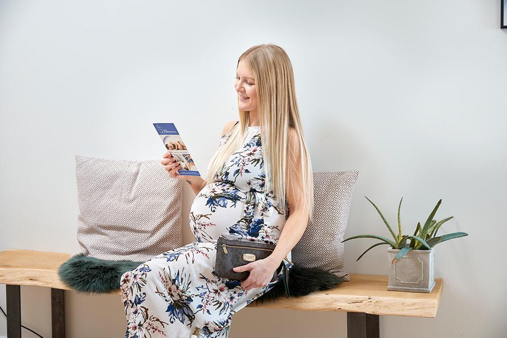 Gravid kvinde kigger på folder i venteværelse på 3d scanning
